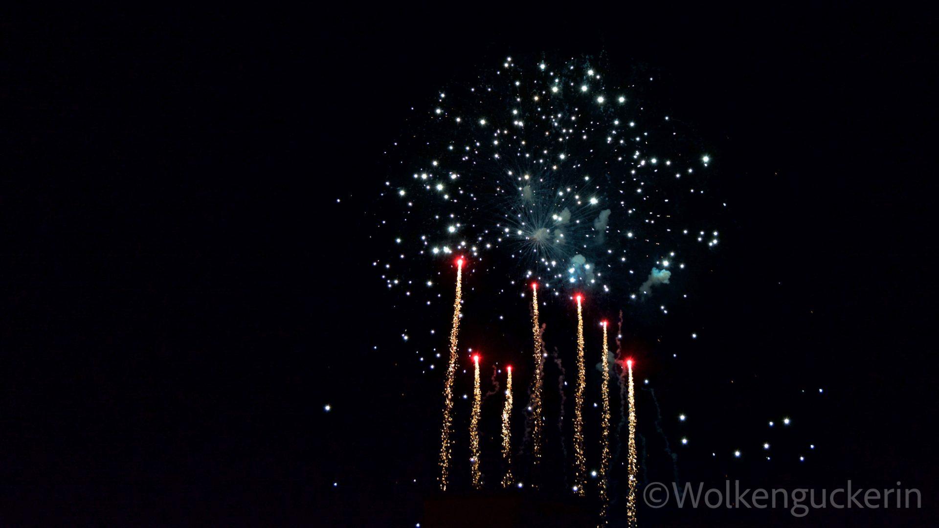 Sieben aufsteigende Raketen am schwarzen Nachthimmel. Dahinter leuchten bereits explodierte Feuerwerksraketen.