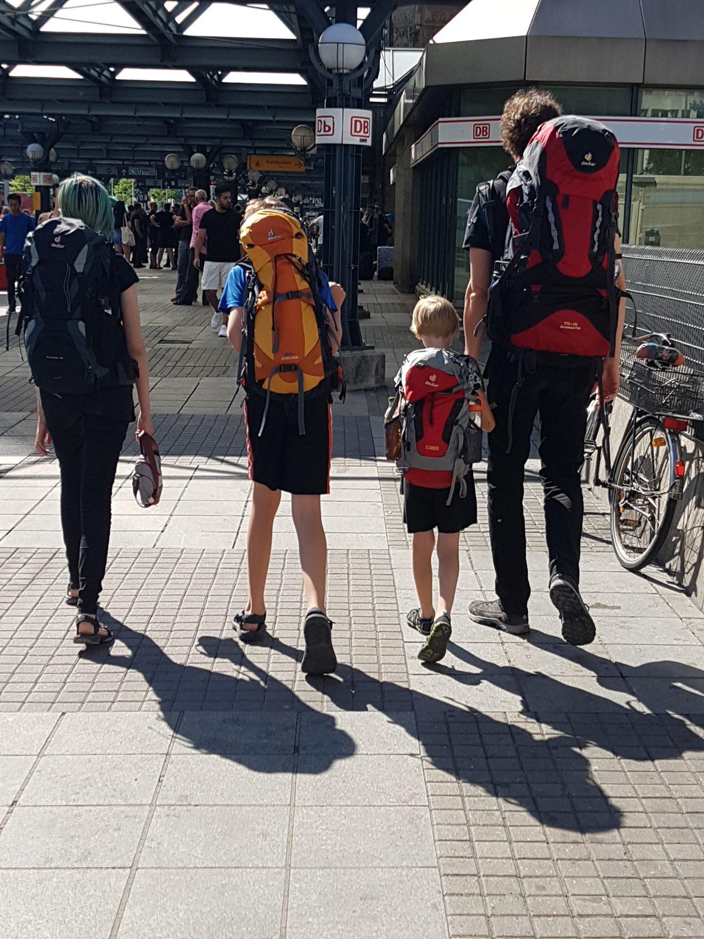 Ein Vater und seine drei Kinder, alle mit Rucksäcken bepackt, laufen in den Hamburger Bahnhof