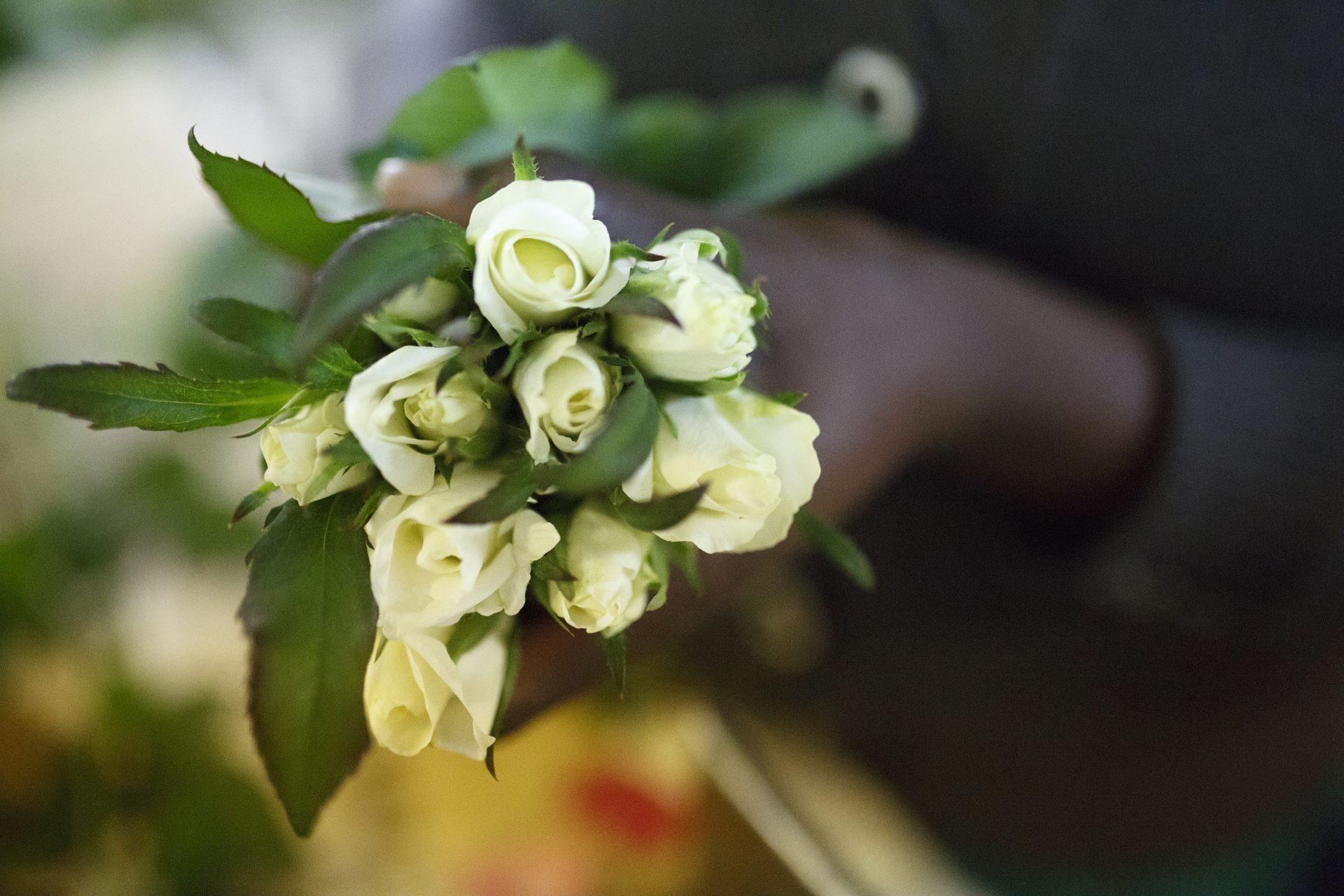faire weiße Rosen in den Händen einer Arbeiterin