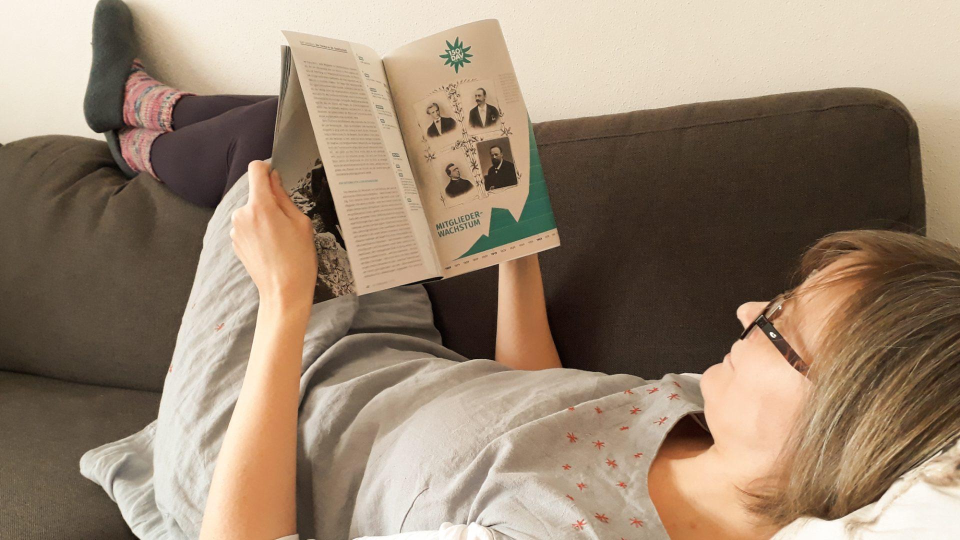 Eine Frau liegt auf dem Sofa und liest in einer Zeitschrift.